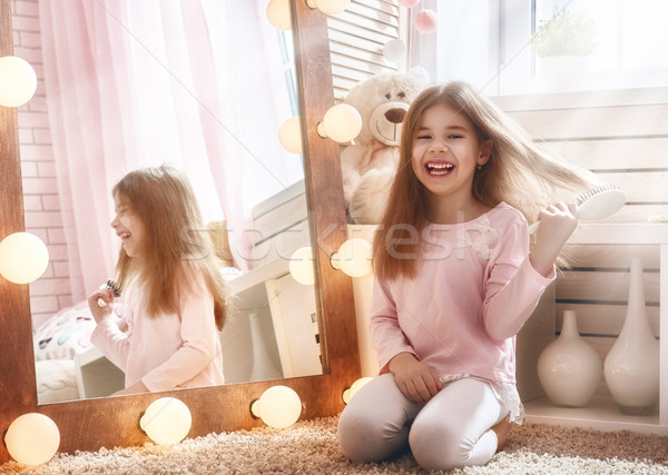 child is combing near mirror Stock photo © choreograph
