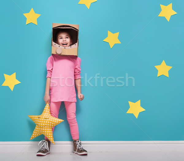 Child girl in an astronaut costume is playing and dreaming of becoming a spacemen. Portrait of funny Stock photo © choreograph