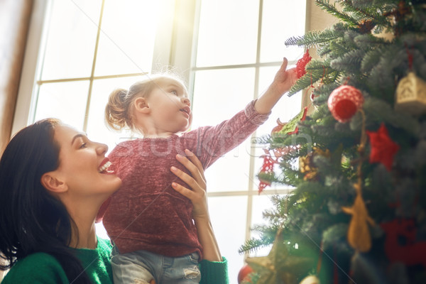 Mom and daughter decorate Christmas tree Stock photo © choreograph