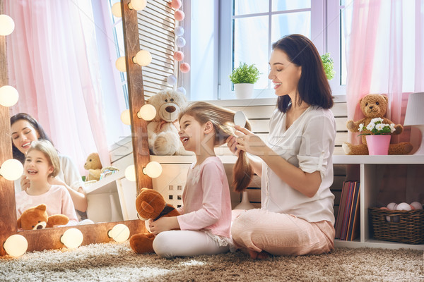 Mother is combing her daughter's hair Stock photo © choreograph