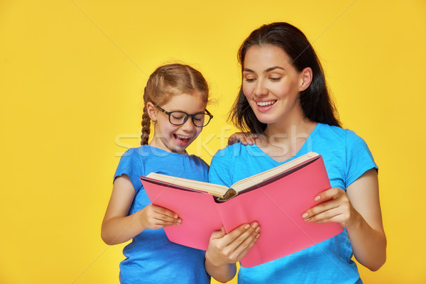 child and mother are reading the book Stock photo © choreograph