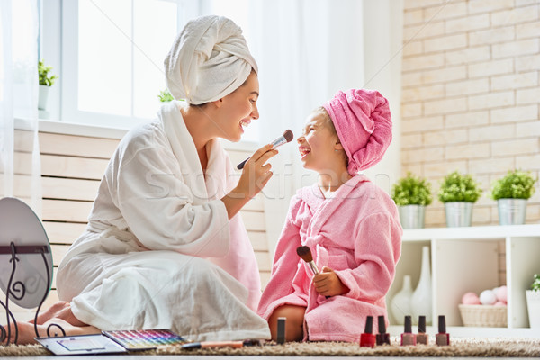 Mother and daughter are doing make up Stock photo © choreograph