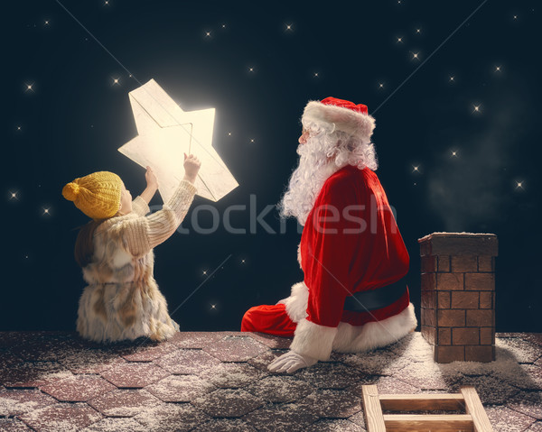 girl and Santa Claus sitting on the roof Stock photo © choreograph
