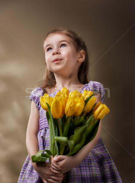 Virág lány kislány citromsárga tulipánok mosoly Stock fotó © choreograph