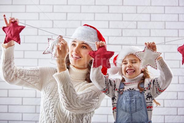 mother and daughter hang a garland Stock photo © choreograph