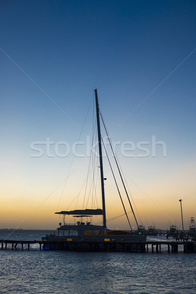 Sunset at marina with docked yacht and calm sea Stock photo © cienpies