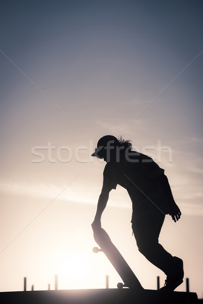 Teenager silhouette doing skateboard trick on ramp Stock photo © cienpies