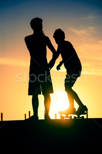Friends silhouette at skate park on summer day Stock photo © cienpies