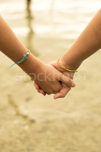 Close up of kids holding hands on beach concept Stock photo © cienpies
