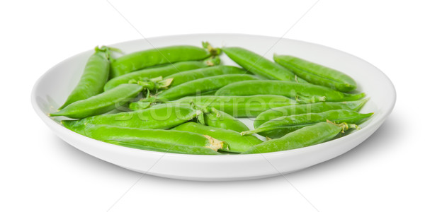 In front several pods of peas on a white plate Stock photo © Cipariss