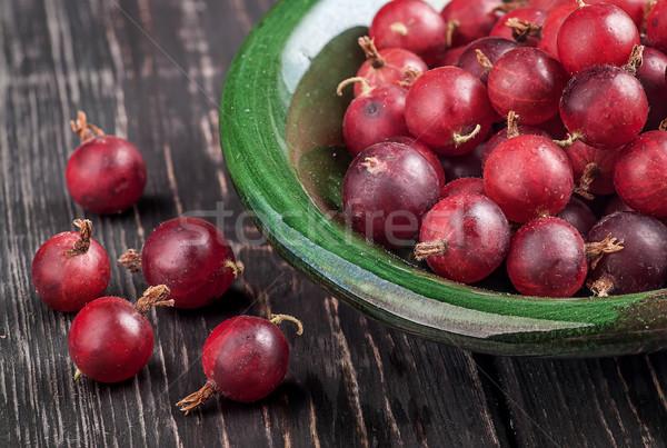 Közelkép piros tál bogyók fa asztal elmosódott Stock fotó © Cipariss
