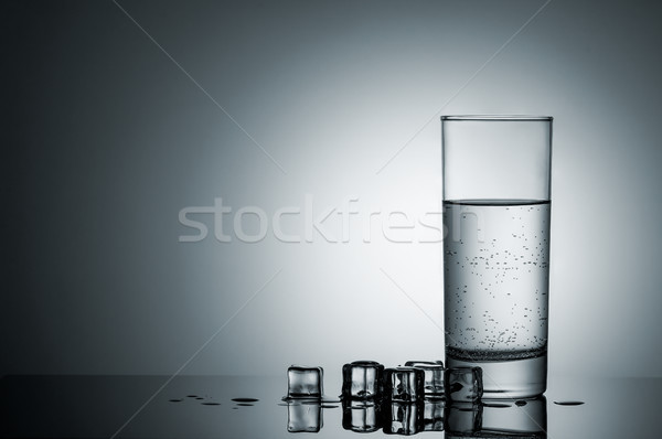 Glass of water and melting ice cubes nearby Stock photo © Cipariss