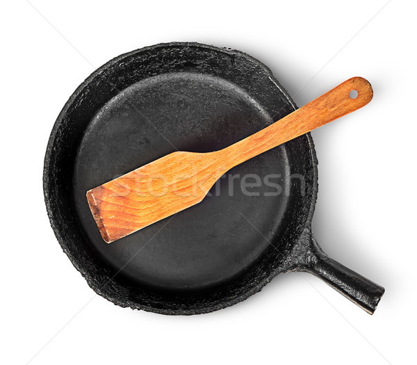 Old cast iron pan with wooden spatula top view Stock photo © Cipariss