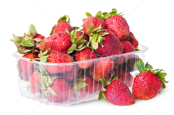 Freshly strawberries in a plastic tray and two near rotated Stock photo © Cipariss