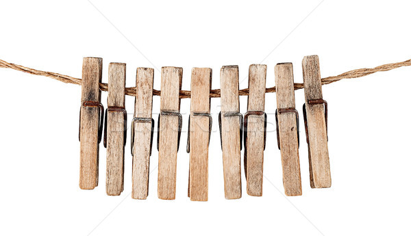 Many old wooden clothespins on a rope isolated Stock photo © Cipariss