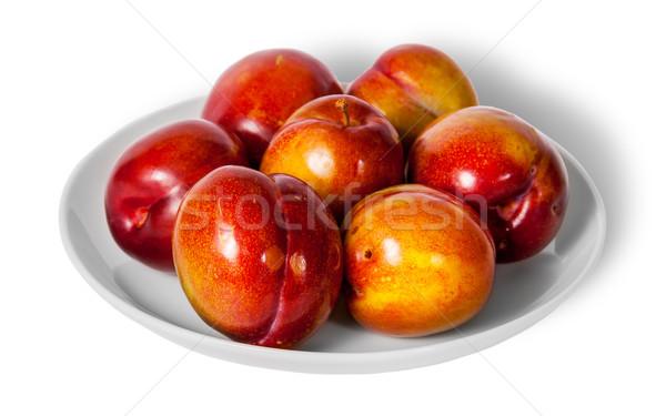Piros citromsárga szilva fehér tányér izolált Stock fotó © Cipariss