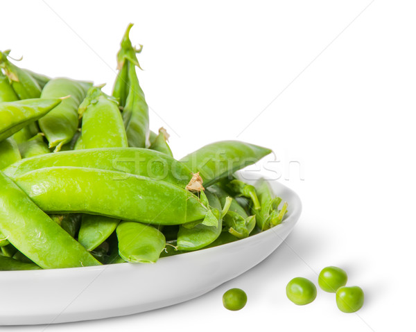 Closeup pile of green peas in pods in white plate Stock photo © Cipariss