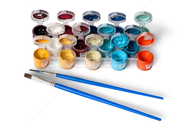 Set of colorful acrylic paints in jars and two brushes Stock photo © Cipariss