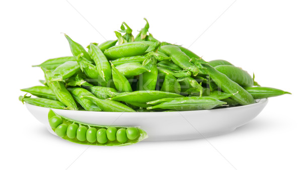 Opening and closing pea pods on white plate Stock photo © Cipariss
