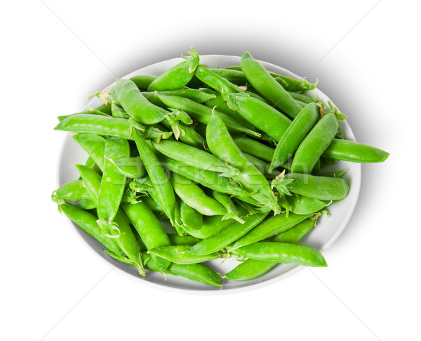 Small pile of green peas in pods on white plate Stock photo © Cipariss