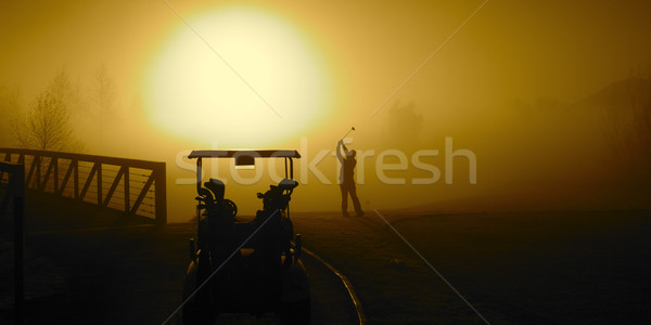 Golfer in the Golden Sunrise fog on a misty morning with a golf  Stock photo © cmcderm1