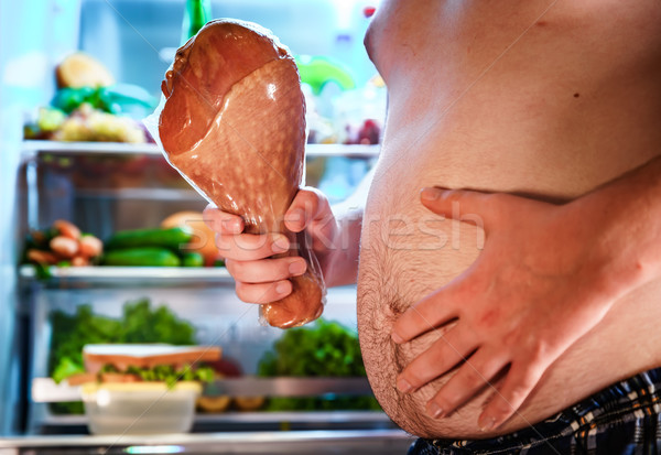 Hungry man holding a turkey leg in his hands and standing next t Stock photo © cookelma