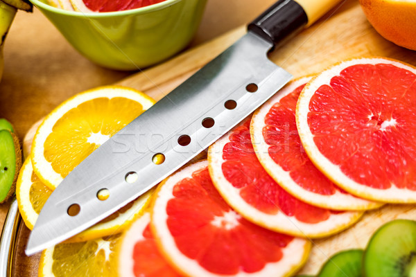 Sharp kitchen knife on cutting Board next to sliced grapefruit a Stock photo © cookelma