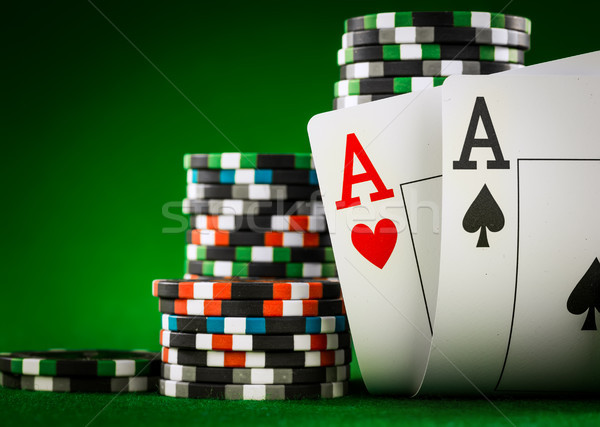 Stack of chips and two aces on the table on the green baize Stock photo © cookelma