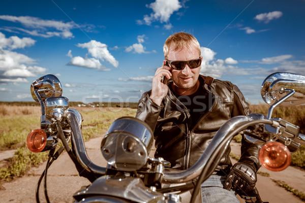 Biker talking on a smartphone. Stock photo © cookelma