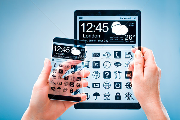 Smartphone and tablet with transparent screen in human hands. Stock photo © cookelma