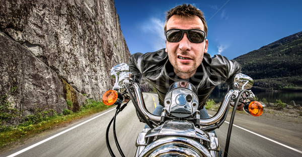 Funny Biker in sunglasses and leather jacket racing on mountain  Stock photo © cookelma