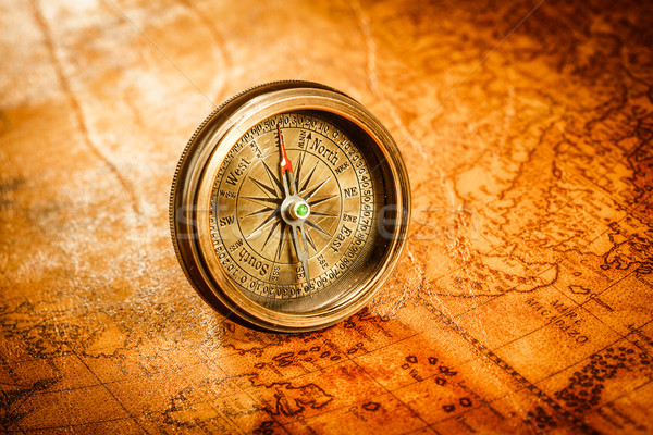 Stock photo: Vintage compass lies on an ancient world map.