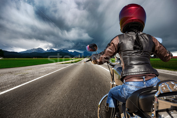 Biker girl on a motorcycle hurtling down the road in a lightning Stock photo © cookelma