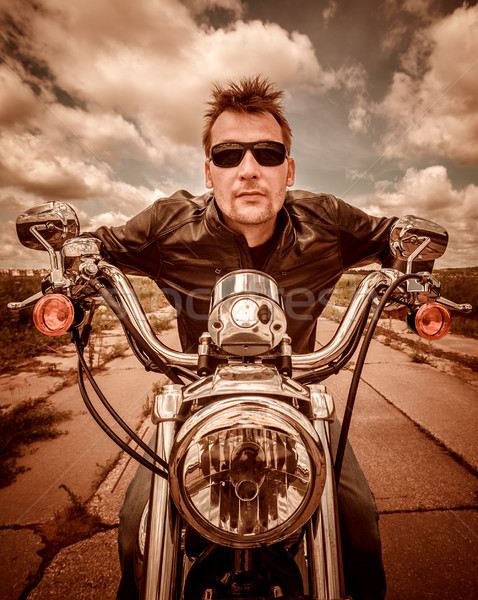 Biker in a leather jacket riding a motorcycle on the road Stock photo © cookelma