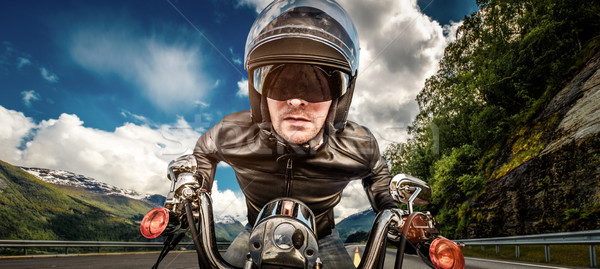Biker in helmet and leather jacket racing on mountain serpentine Stock photo © cookelma