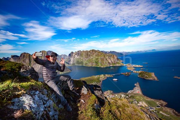 Man on top of a mountain taking a selfie Stock photo © cookelma