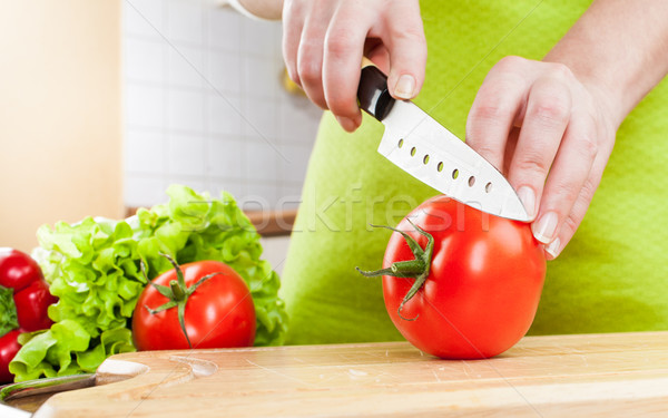 Stock photo: Woman's hands cutting tomato