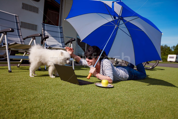 Woman on the grass with a dog looking at a laptop Stock photo © cookelma