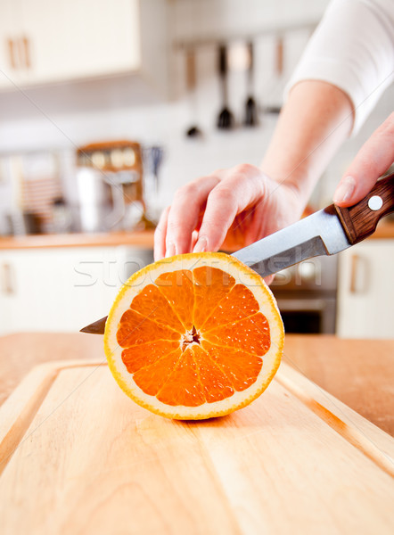 Stock photo: Woman's hands cutting orange