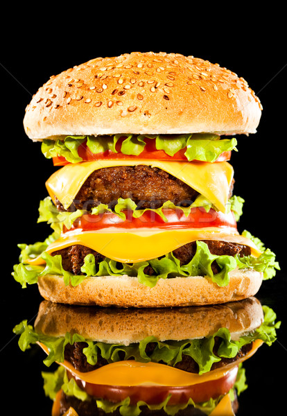 Stock photo: Tasty and appetizing hamburger on a dark