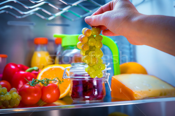 Woman takes the bunch of grapes from the open refrigerator Stock photo © cookelma