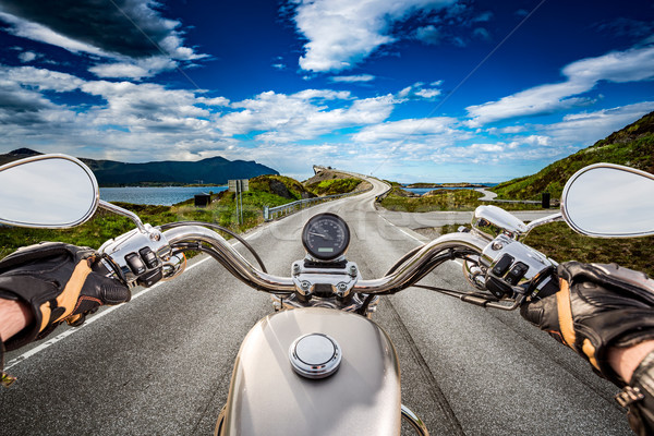 Biker rides a road with Atlantic Ocean Road in Norway. First-per Stock photo © cookelma