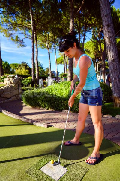 Mini Golf - Woman playing Golf on green grass at sunset Stock photo © cookelma