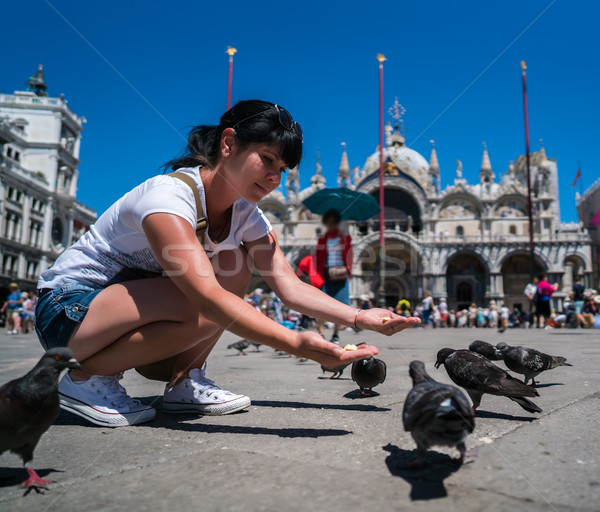 Woman tourist feeding pigeons in the square - St. Marks Square - Stock photo © cookelma