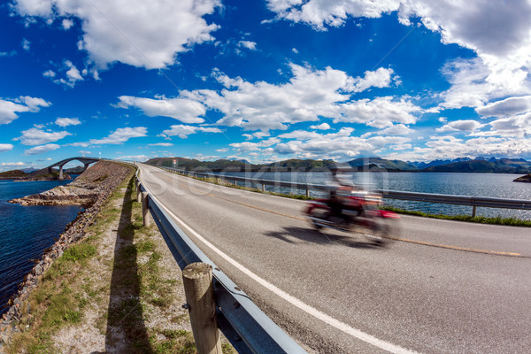 Biker rides a road with Atlantic Ocean Road in Norway. Stock photo © cookelma