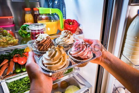 Human hands reaching for sweet cake at night in the open refrige Stock photo © cookelma