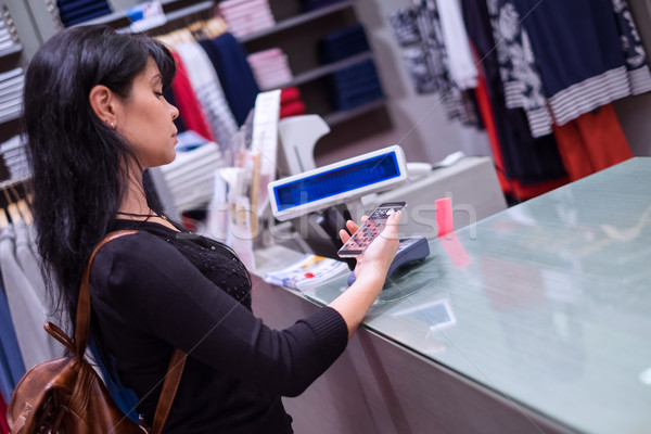 Mobile payment. Girl pays to shop using mobile phone Stock photo © cookelma