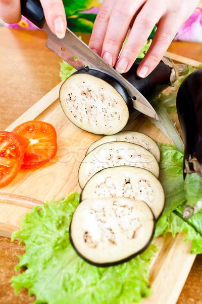Stock photo: Woman's hands cutting aubergine eggplant