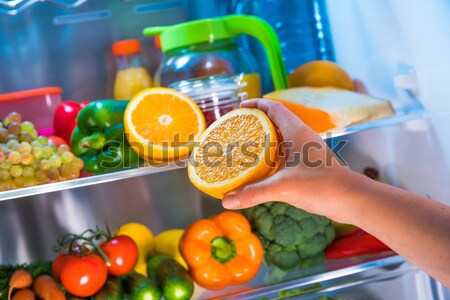 Human hands reaching for food at night in the open refrigerator Stock photo © cookelma