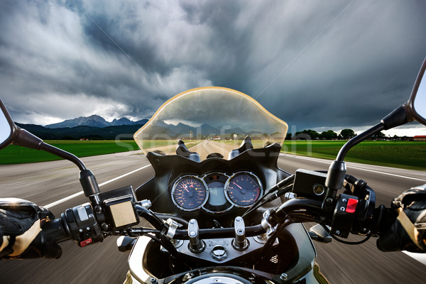 Biker on a motorcycle hurtling down the road in a lightning stor Stock photo © cookelma